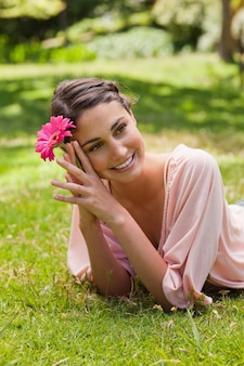 Woman lying on her front while holding a flower against her head