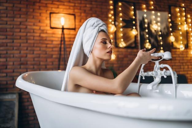 彼女の頭にタオルで白いお風呂に横たわっている女性