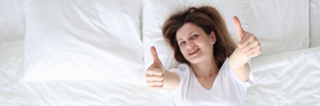 Женщина, лежащая в постели и показывающая большие пальцы вверх, вид сверху, отличное начало дня, концепция