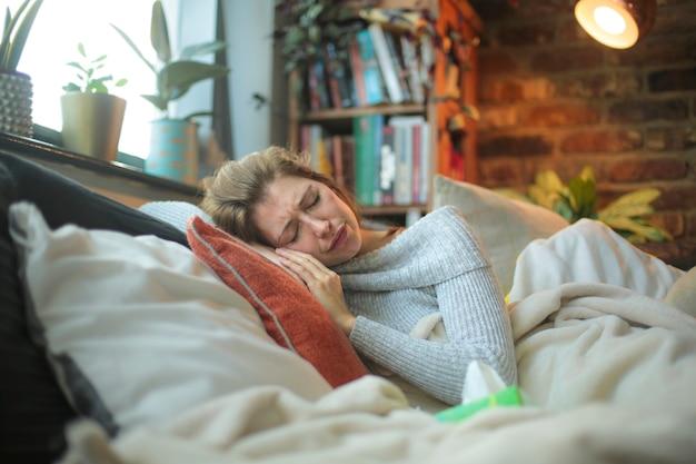 Женщина лежит в постели, чувствуя себя больным. выздоравливает от covid-19 в условиях самоизоляции.
