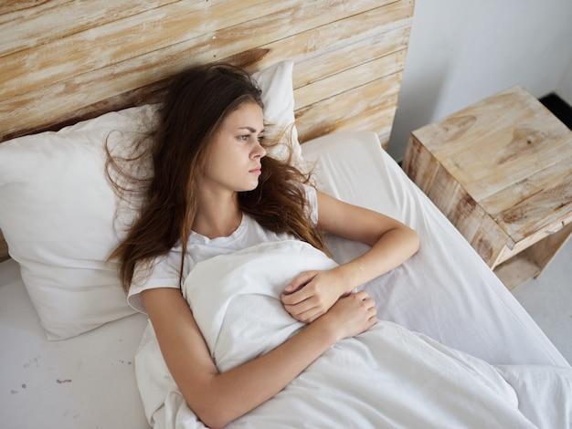 침대에 누워있는 여자 슬픈 표정 불만