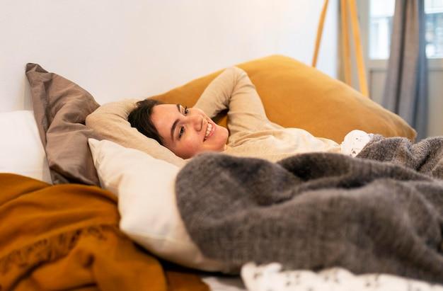 リラックスするためにベッドに横たわっている女性