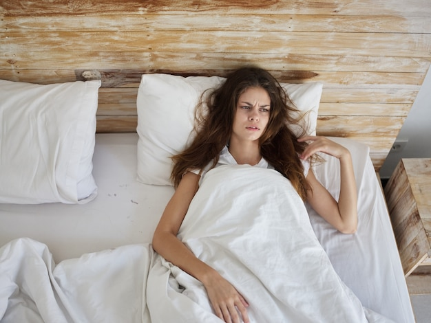 커버 아래 침대에 누워있는 여자 불만족스러운 생활 방식