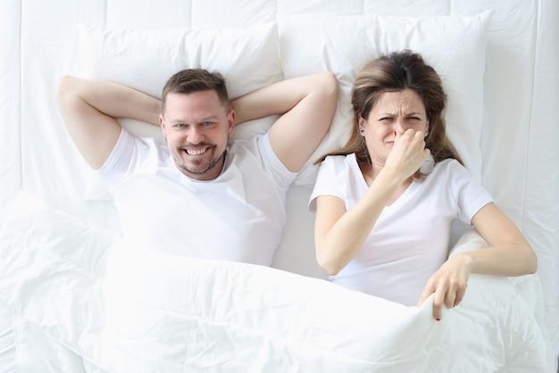 男性と一緒にベッドに横たわり、彼女の手で彼女の鼻を覆っている女性。増加したガス形成の概念