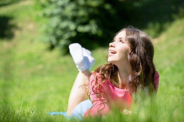 草で横になっていると笑顔の女性