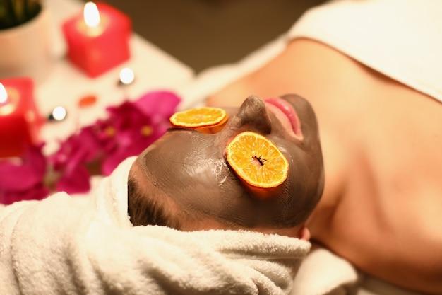 Женщина лежит в спа-салоне с глиняной маской на лице и дольками апельсина на глазах