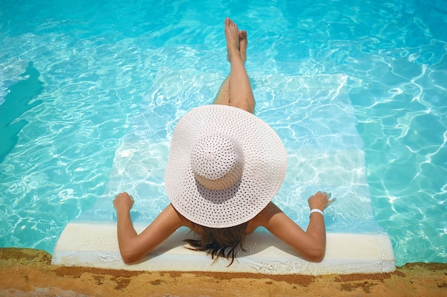 Woman lying on a lounger in pool at hotel