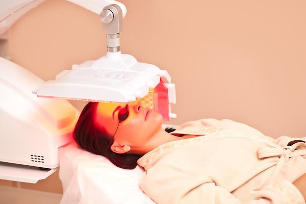 目の保護メガネをかけたテーブルに横になっている女性は、美容装置の下でスキントリートメントを受けています。ビューティースパサロン。