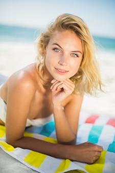 여자는 해변에서 수건에 누워