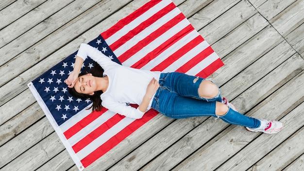 Женщина, лежащая на американском флаге