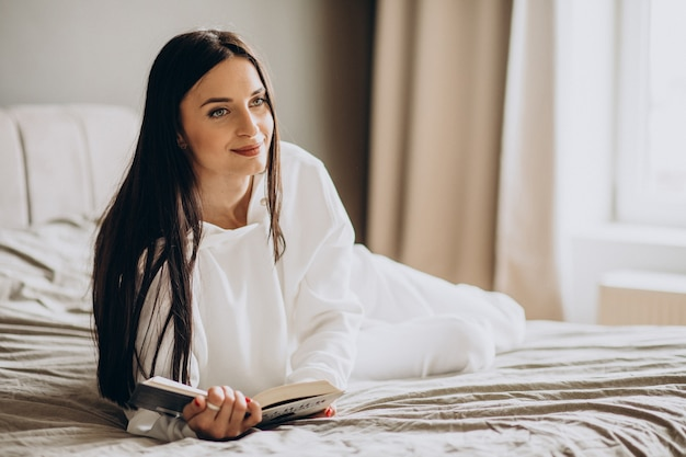 Женщина, лежа на кровати и читающая книгу