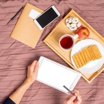 침대에 누워, 차를 마시고, 태블릿을보고, 구매, 온라인 쇼핑을 지불합니다.