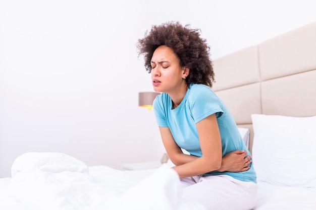 リビングルームで病気に見えてベッドに横たわる女。若い女性はベッドに横になっていると彼女の胃に手を繋いでいます。