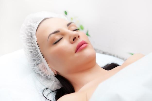 Женщина, лежа на кровати во время инъекции красоты в шею. процедуры для лица. концепция красоты.
