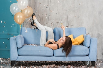 Woman lying on blue couch with champagne