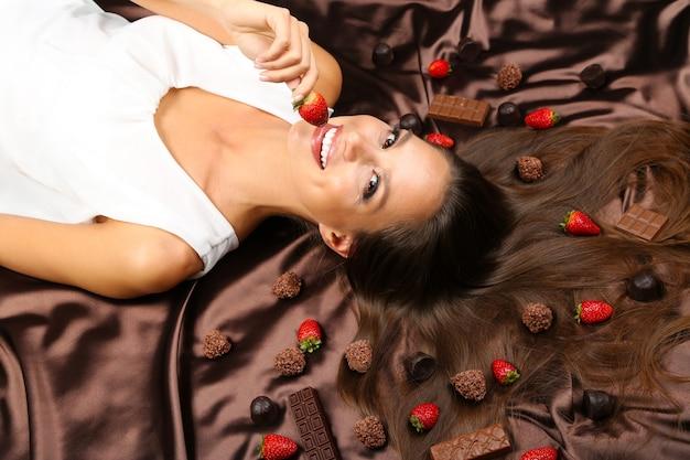 Женщина, лежащая на коричневом атласе, покрытом шоколадом и конфетами