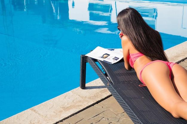 Женщина лежит на шезлонге и читает журнал возле бассейна на открытом воздухе