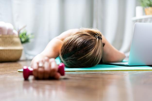 Женщина лежит на полу и отдыхает после тренировки дома