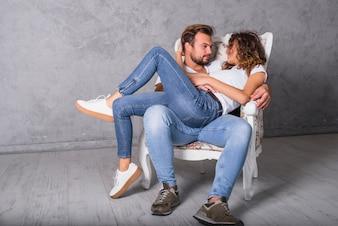 Woman lying on man in armchair