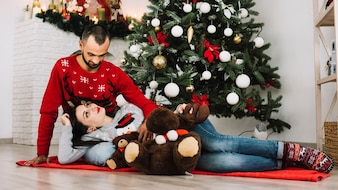 Woman lying on man near soft toys