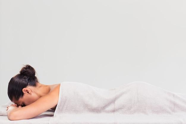 Женщина, лежащая на массажном шезлонге