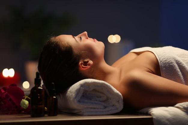 暗いスパルームのマッサージテーブルに横たわっている女性。美容業界のボディケアコンセプト