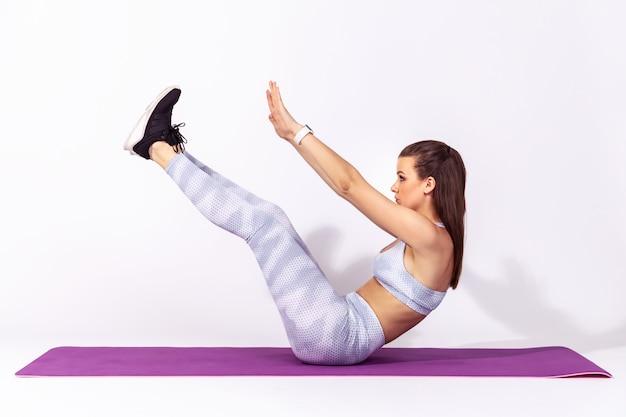 Женщина лежит на резиновом коврике для йоги, поднимая руки и ноги, делая скручивания, накачивая живот