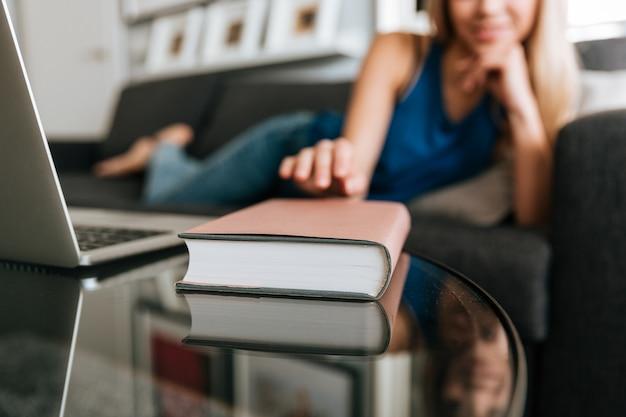 Женщина лежит на диване и берет книгу со стола