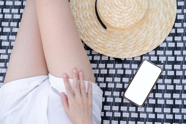 Женщина, лежа на кровати для загара с мобильным телефоном и пустым белым экраном на пляже.