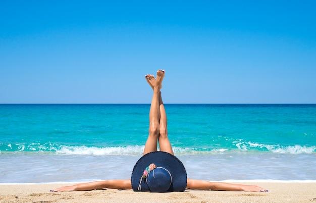 空中に足を上げてビーチに横たわっている女性