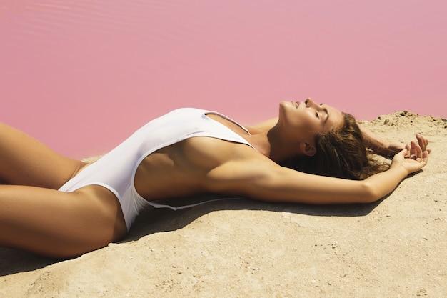 Женщина лежит на пляже с розовой водой