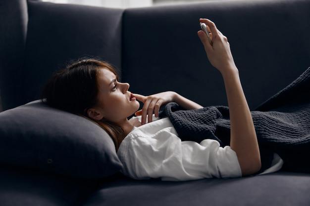 Женщина лежит на диване с мобильным телефоном в руке, вид сбоку