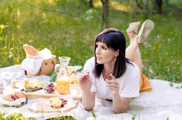 公園の芝生の上に横たわって、一日を楽しんでいる女性。レジャー、休暇の概念