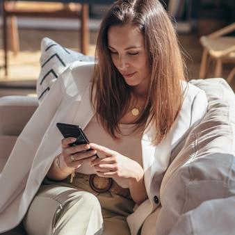 여자는 소파에 누워 집에서 스마트 폰을 사용합니다.