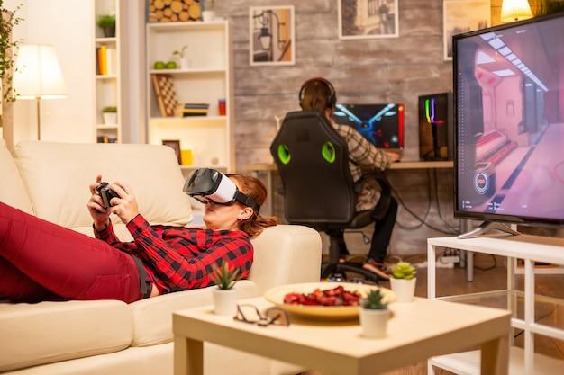 Женщина, лежа на диване поздно ночью в гостиной, играет в видеоигры с помощью гарнитуры виртуальной реальности