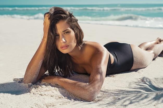 白い砂の上に横たわる女