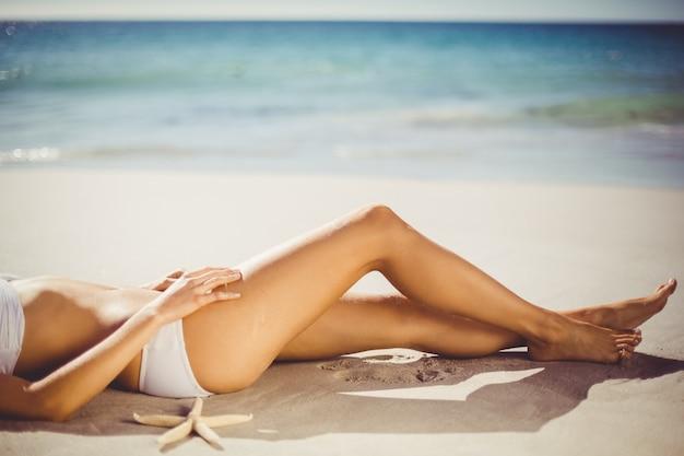 Woman lying on sand alone