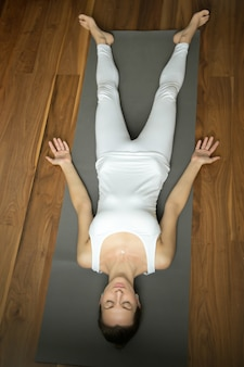 Woman lying in savasana pose