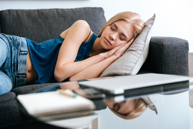 Woman lying and sleeping on couch at home
