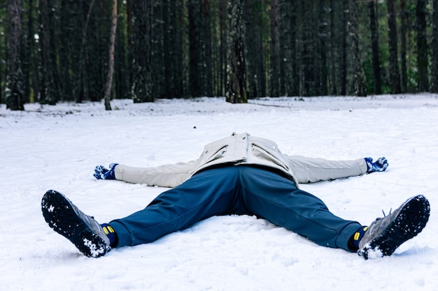 Woman lying on the snow-covered forest floor