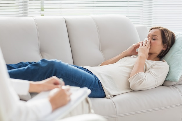 Woman lying on sofa by therapist