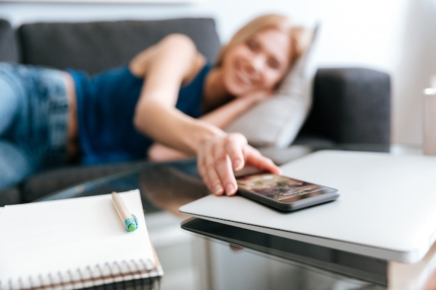 Woman lying on sofa and taking mobile phone from table