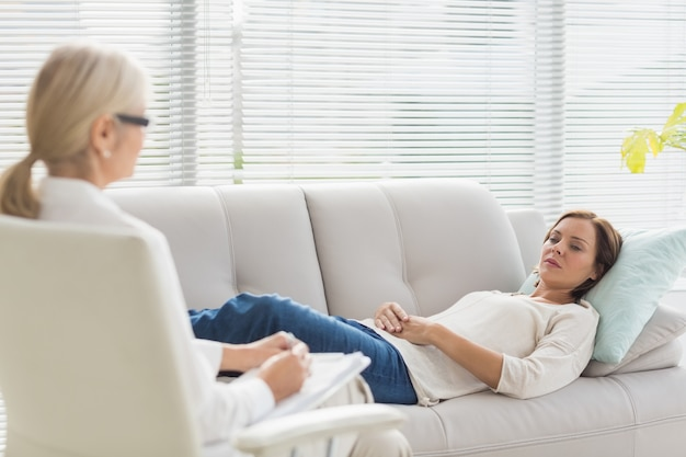 Woman lying on sofa while talking to therapist