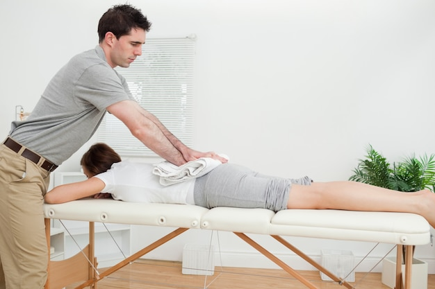 Woman lying while being massaged with a towel