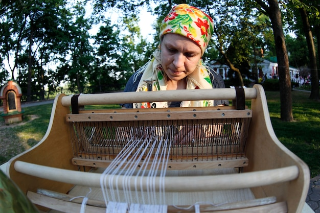 The woman at the machine is spinning yarn