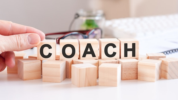 Woman made word coach with wood blocks. selective focus.