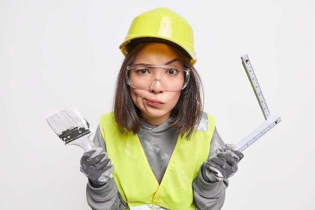 Женщина-ремонтник держит кисть и рулетку, ухмыляется, лицо носит защитный шлем и униформу, изолированные на белом