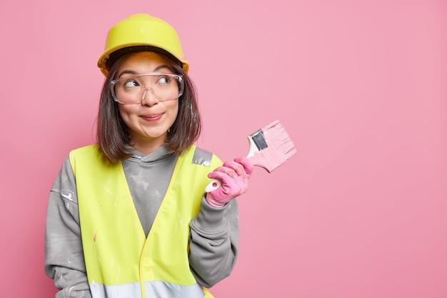 여자 유지 보수 작업자는 그림 도구를 들고 꿈꾸는 듯한 표정으로 시선을 멀리하며 아파트를 어떻게 장식할지 생각합니다 보호용 헬멧 유니폼과 보안경을 착용합니다