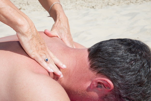 Woman make back massage to man in sand