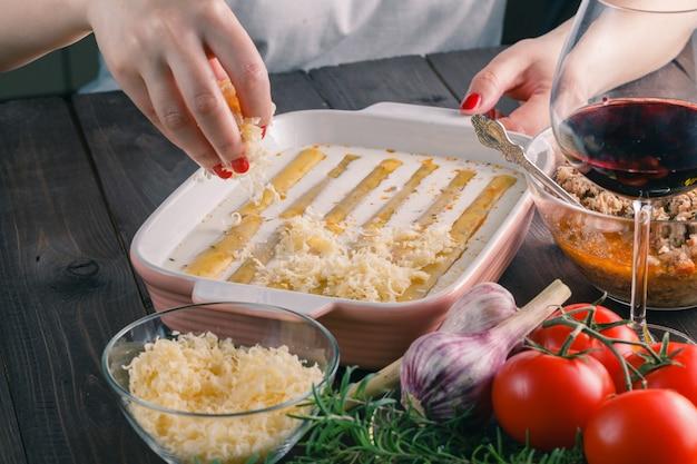 Женщина делает каннеллони с сыром